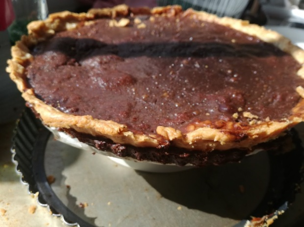 Baked, cooling chocolate tart on a stand